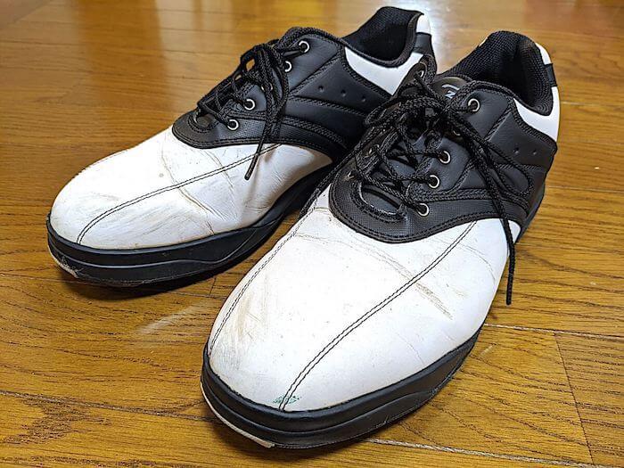 白と黒のゴルフスパイクは薄汚くなっています。